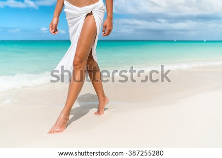 Caribbean vacation travel - woman leg closeup walking on white sand relaxing in beach cover-up pareo beachwear. Sexy lean and tanned legs. Sunmmer holidays, weight loss or epilation concept.