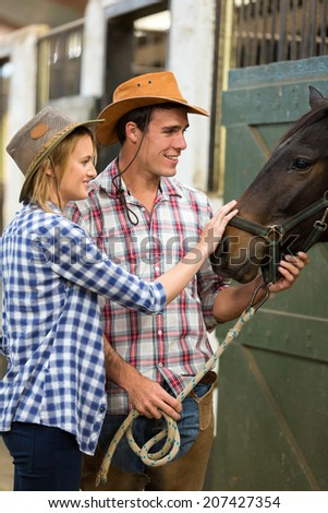 caring cowboy and cowgirl in stable touching a horse