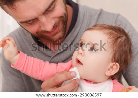 Caring daddy. Pleasant young father touching child with napkin and smiling while holding baby on knees.
