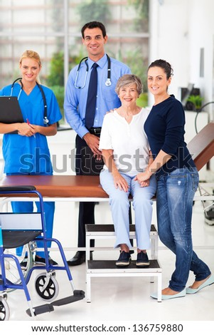 caring daughter taking senior mother for checkup in doctor's office - stock photo
