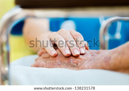 Caring doctor or nurse holding elderly lady's hands in wheelchair. - stock photo