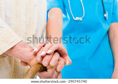 Caring doctor supporting elderly patient in her struggle - residential care. - stock photo