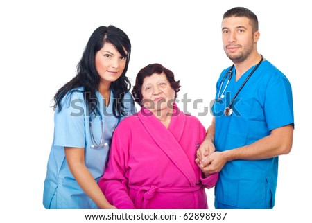 Caring doctors holding hands of elderly woman patient and helping her to walk isolated on white background - stock photo