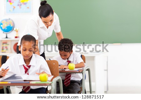 caring elementary school teacher and students in classroom