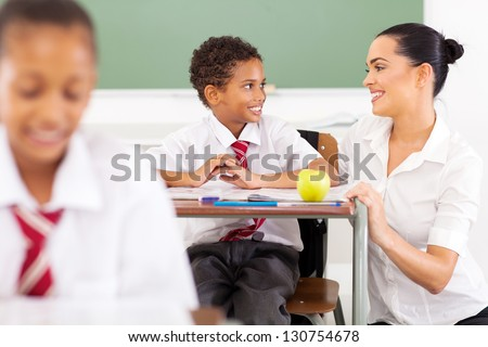 caring elementary school teacher talking to a student in classroom - stock photo