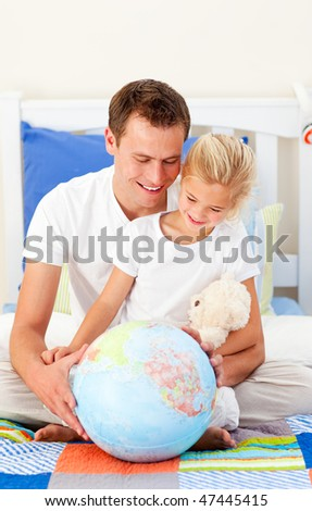 Caring father and his daughter looking at a terrestrial globe sitting on bed