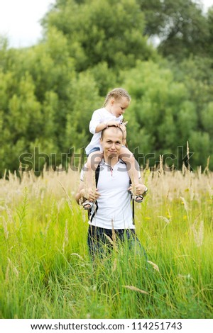 Caring father carrying daughter on his neck while walking outdoors on a meadow