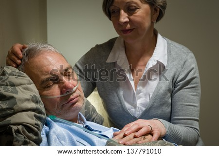 Caring female nurse with sleeping senior male patient - stock photo