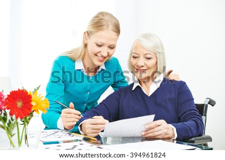 Caring for senior woman with wheelchair in family with granddaughter - stock photo
