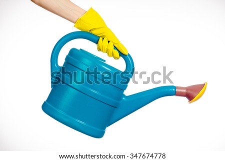 Caring for the plants and the garden theme: the human hand in yellow rubber gloves holding a large blue plastic watering can isolated on white background in studio