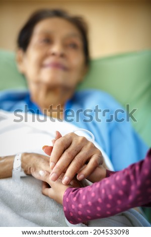 Caring hands holding kind elderly lady's hands in bed at hospital - stock photo