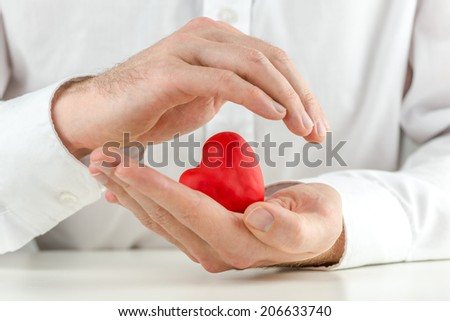 Caring man cupping a red heart in his hands with one hand held protectively over the top in a love, romance and nurturing concept. - stock photo
