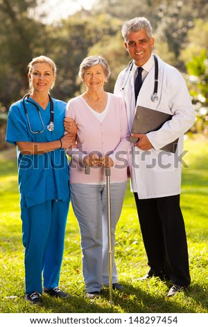 caring medical staff and senior patient outdoors - stock photo