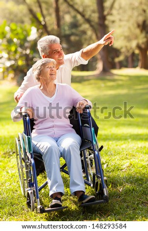 caring mid age son taking senior mother for a walk