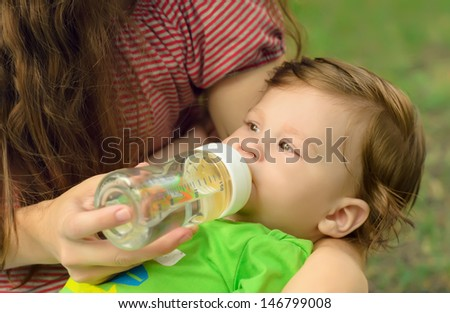Caring mother gives son drink water bottles on lawn in summer park - stock photo