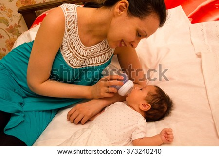 caring mother kissing baby daughter while she drinking milk - stock photo
