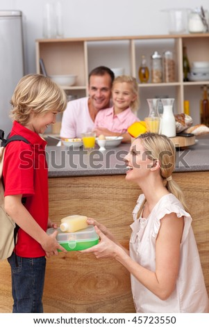 Caring mother packing the school lunch to his son in the kitchen