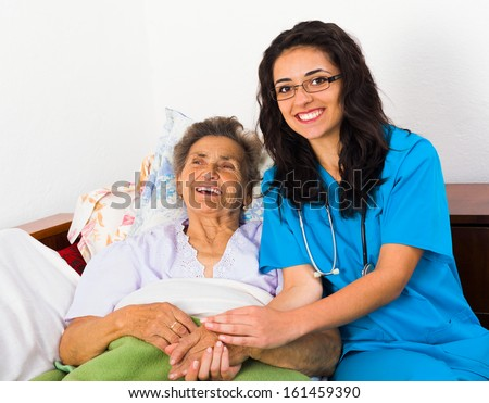 Caring nurse having fun with kind elderly patient. - stock photo