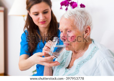 Caring nurse helping sick elderly woman to drink in bed in a nursing home. - stock photo
