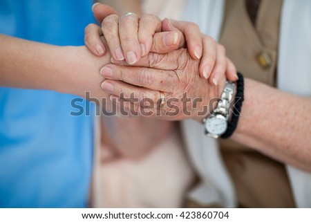 Caring nurse holding old woman hands - stock photo