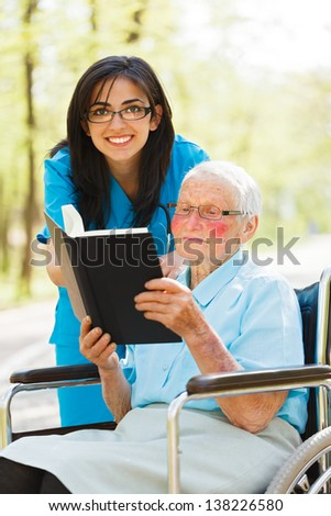 Caring nurse outdoors with elderly lady reading the bible.