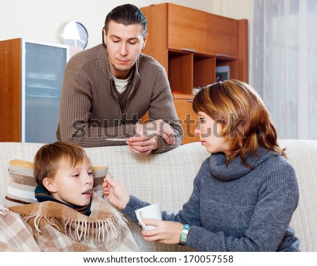 caring parents giving medicinal sirup to teenage son at home