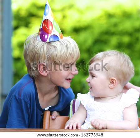 Caring teenager boy celebrating first birthday of his sister, one year old baby girl - stock photo
