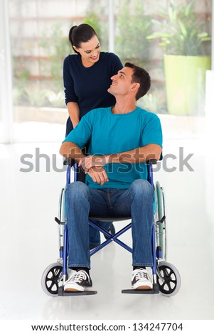 caring wife talking to disabled husband at home