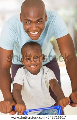 caring young african father pushing son on a bike