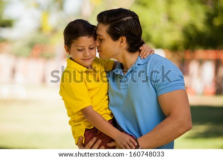 Caring young father carrying and embracing his little boy while hanging out in a park