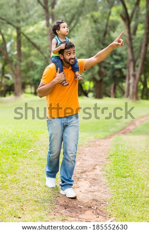 caring young indian father and son walking outdoors in forest - stock photo