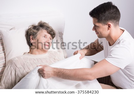 Caring young man covering grandmother with warm blanket