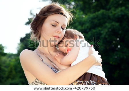 Caring young mother hugged the child on the nature
