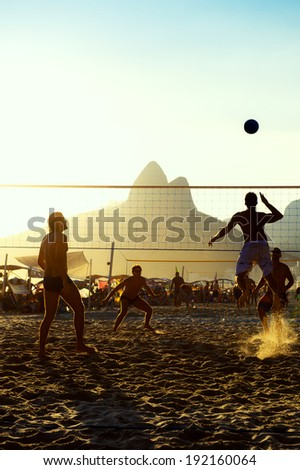Carioca Brazilians Rio de Janeiro Brazil sunset beach volleyball game against a silhouette of Dois Irmaos Mountain on Ipanema Beach - stock photo