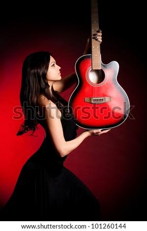 Carmen beautiful woman with guitar on dark background - stock photo