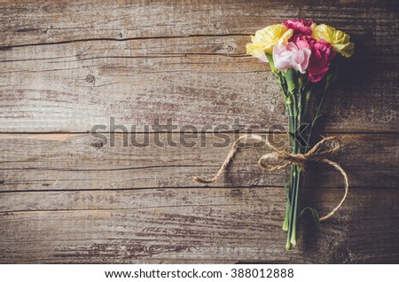 Carnation flowers on wooden table - stock photo