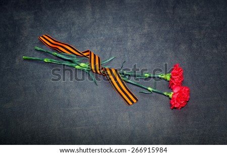 Carnations and St. George ribbon on a dark background. May 9 Victory Day - stock photo