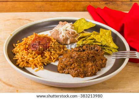 Carne Guisada in rustic restaurant setting on plate with Spanish Rice and refried beans and spicy jalapeno tortilla chips. - stock photo