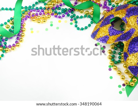 Carnival and Mardi Gras items including harlequin mask, green, gold and purple beads and ribbons and confetti on a warm white background. Copy space for your message. Horizontal composition