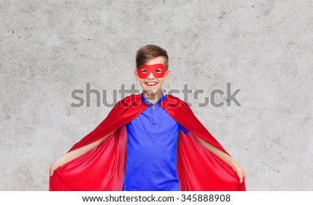 carnival, childhood, power and people concept - happy boy in red super hero cape and mask over gray background - stock photo