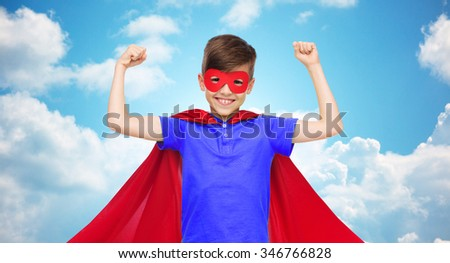 carnival, childhood, power, gesture and people concept - happy boy in red super hero cape and mask showing fists over blue sky and clouds background - stock photo