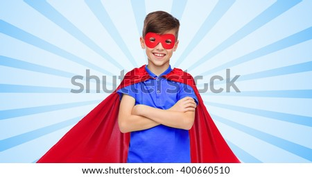 carnival, childhood, power, gesture and people concept - happy boy in red super hero cape and mask over blue burst rays background - stock photo