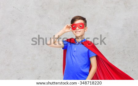 carnival, childhood, power, gesture and people concept - happy boy in red superhero cape and mask over gray concrete background - stock photo