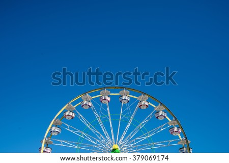 Carnival Ferris Wheel with Clean Skies with Empty Space Close up shot of half of a ferris wheel in Coachella California. - stock photo