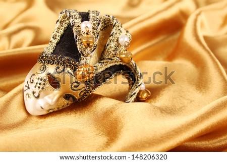 Carnival mask lying on a yellow silk - stock photo