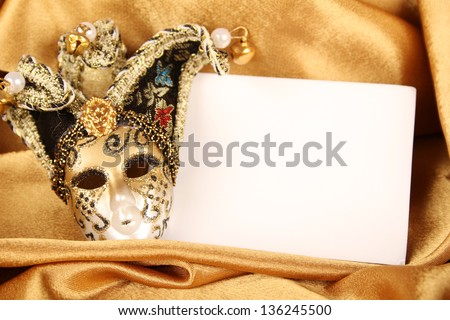 Carnival mask lying on a yellow silk and a sheet of white paper - stock photo