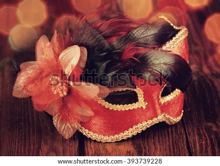 Carnival mask on an old wooden table, toned in red - stock photo