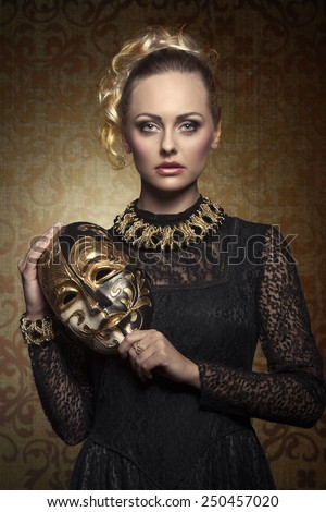 carnival portrait of blonde woman with aristocratic antique lady mask, elegant lace dress and baroque jewellery. Venetian mask in the hand  - stock photo