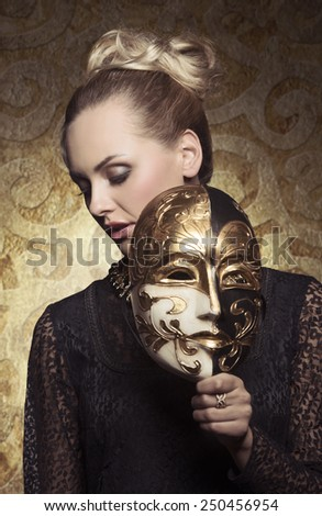 carnival portrait of masquerade blonde woman with antique baroque lady style and venetian mask in the hand. Gothic lace dress and precious jewellery  - stock photo