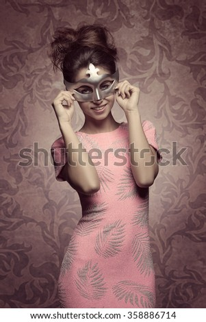 carnival portrait of sexy brunette girl with happy expression masquerade with silver mask, posing with hair style and pink sexy dress  - stock photo